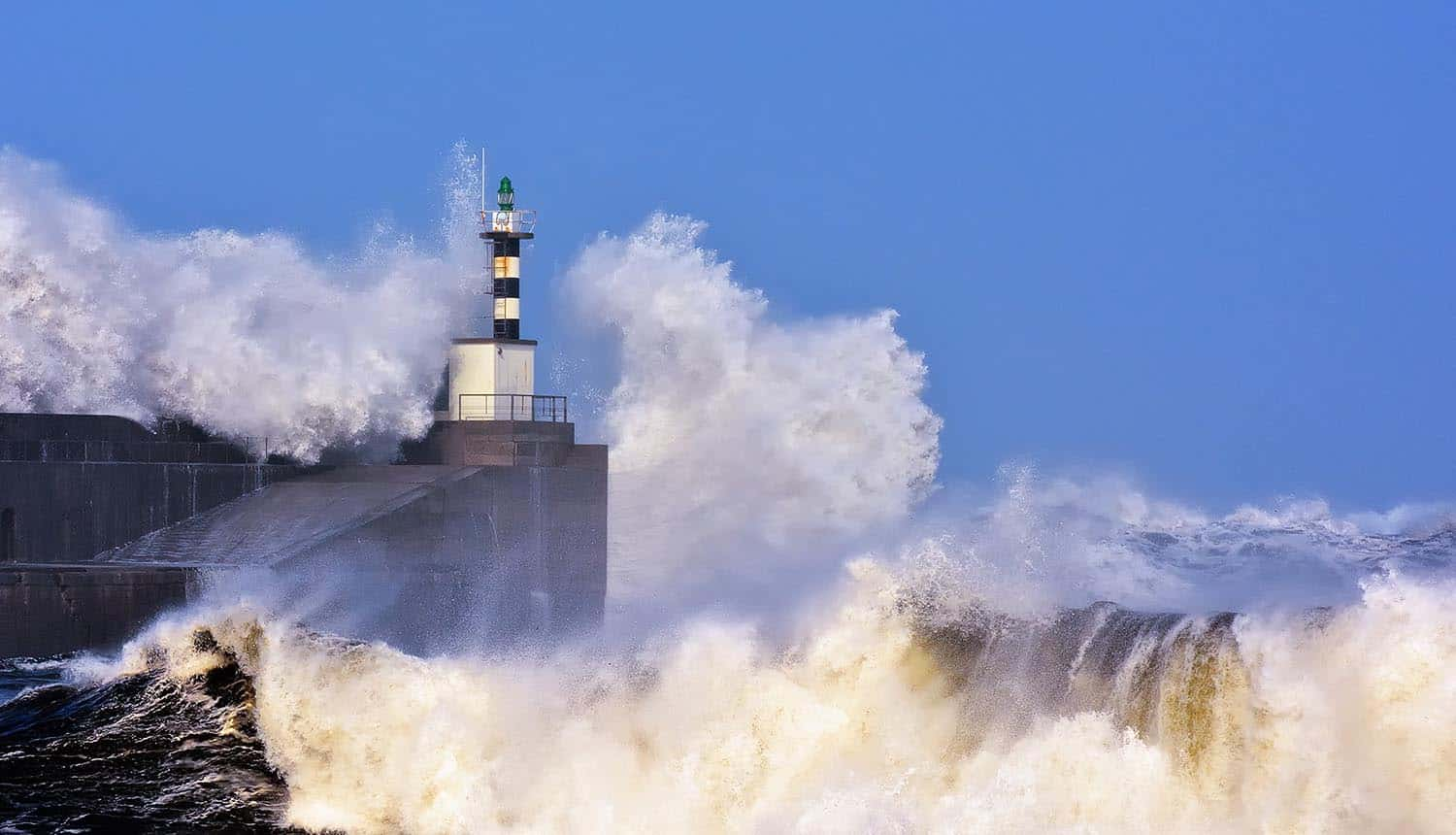 Image of waves crashing on rocks around lighthouse signifying the waves of DDoS attack and the different attack vectors