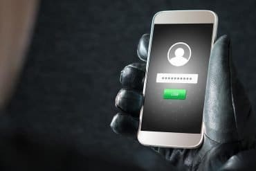 Image of gloved hand holding mobile phone showing login screen signifying Fakebank Android malware and the threat of vishing attacks