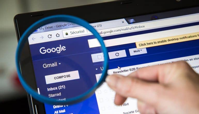 Image of magnifying glass on laptop screen with Gmail window signifying legal attack on Gmail privacy practices