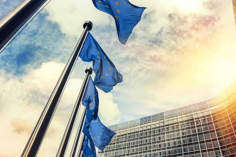 Image of European Union flags in front of building signifying considerations of legitimate interests for GDPR privacy compliance