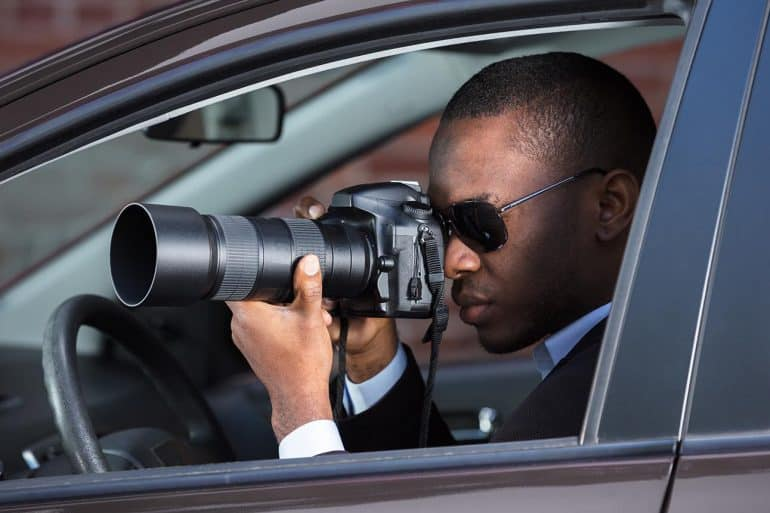Image of man sitting in a car holding a camera with zoom lens signifying the use of online behavioral tracking for spying on users