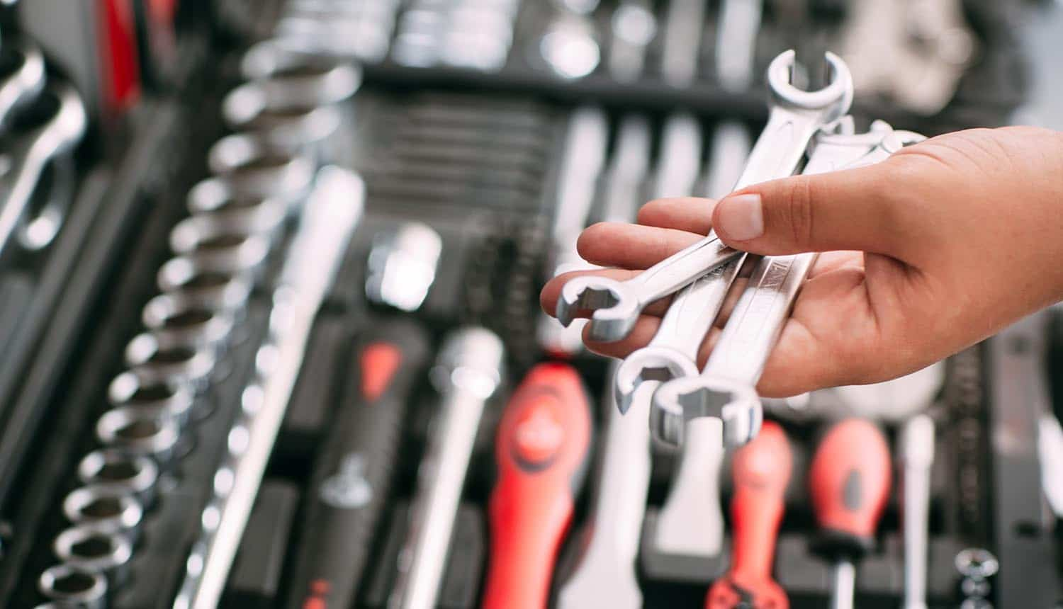 Image of man holding spanners above a toolbox signifying the must-have security tools for achieving GDPR compliance