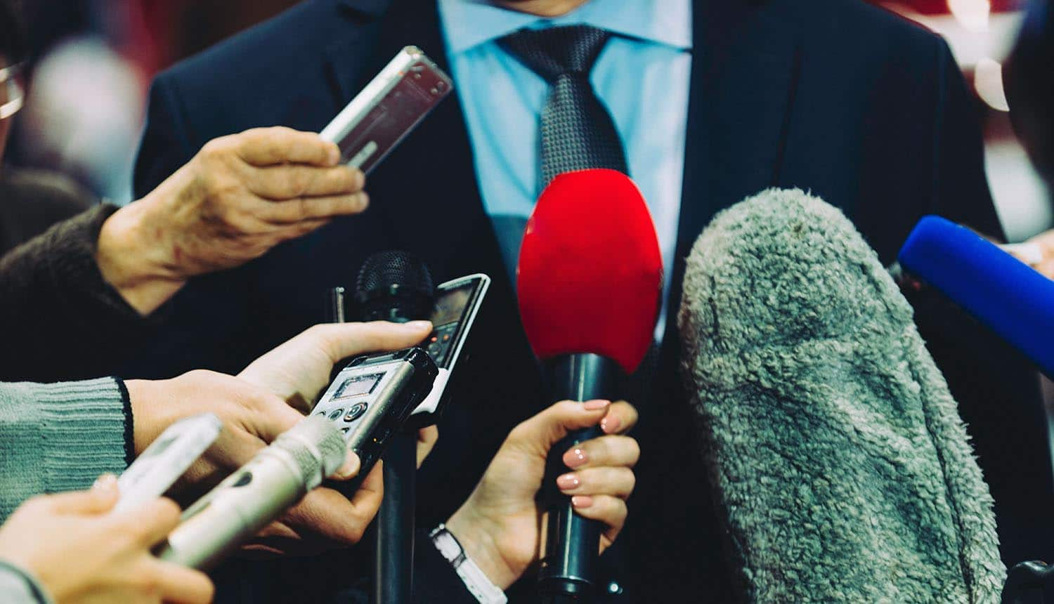 Image of man wearing a tie in front of microphones doing a media interview on data breaches for Under Armour and Panera Bread