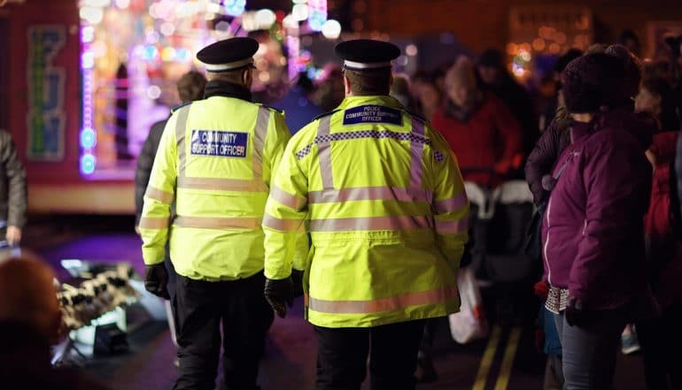 Image of two policemen walking along the street with onlookers signifying predictive policing and how that may result in biased arrests