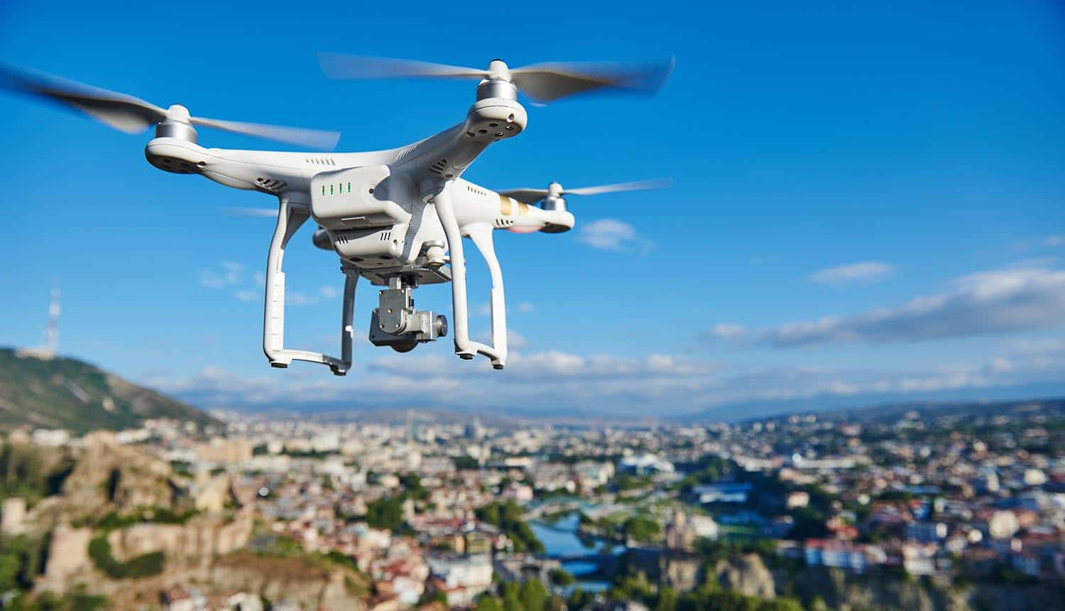 Image of drone flying as a eye in the sky against city backdrop signifying drone surveillance and the concern with privacy