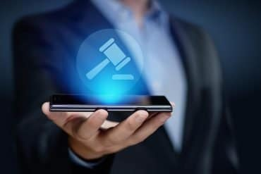 Image of man holding a smartphone with image of hammer representing privacy legislation emerging to govern technology in the wake of the Facebook Cambridge Analytica case