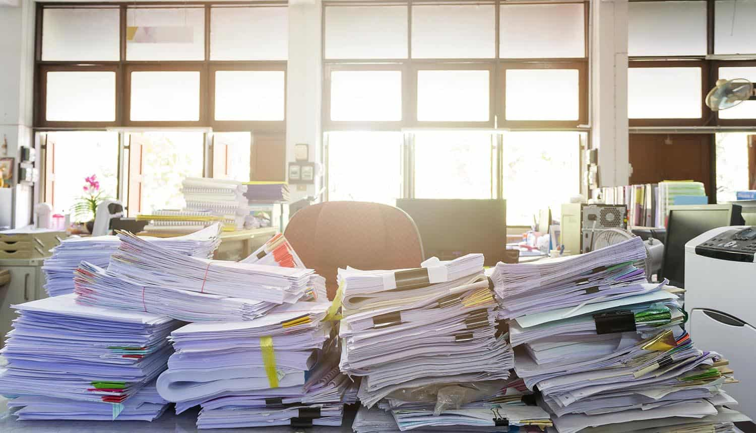 Image of office desk with piles of paperwork signifying the need for buying privacy office support software