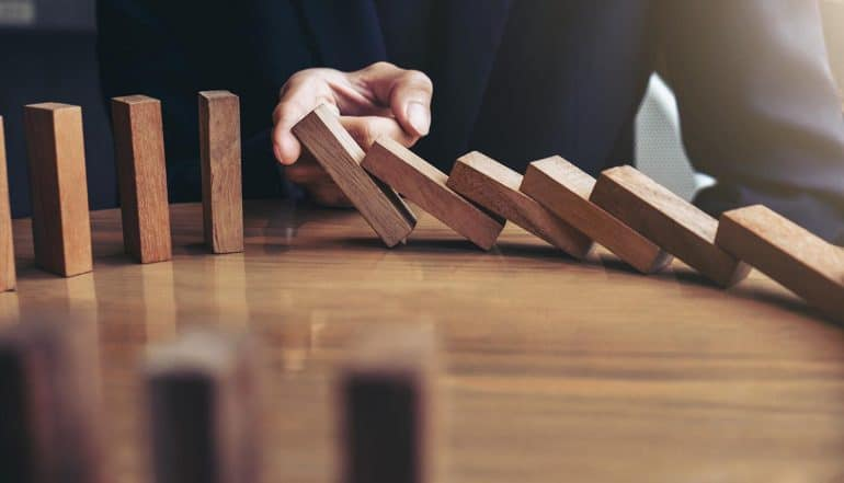 Image of man using finger to stop blocks falling like dominos signifying how contracted service providers can take down your business