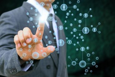 Image of man using his finger to select a person in a network showing how privacy might not be dead but may be difficult to get it back