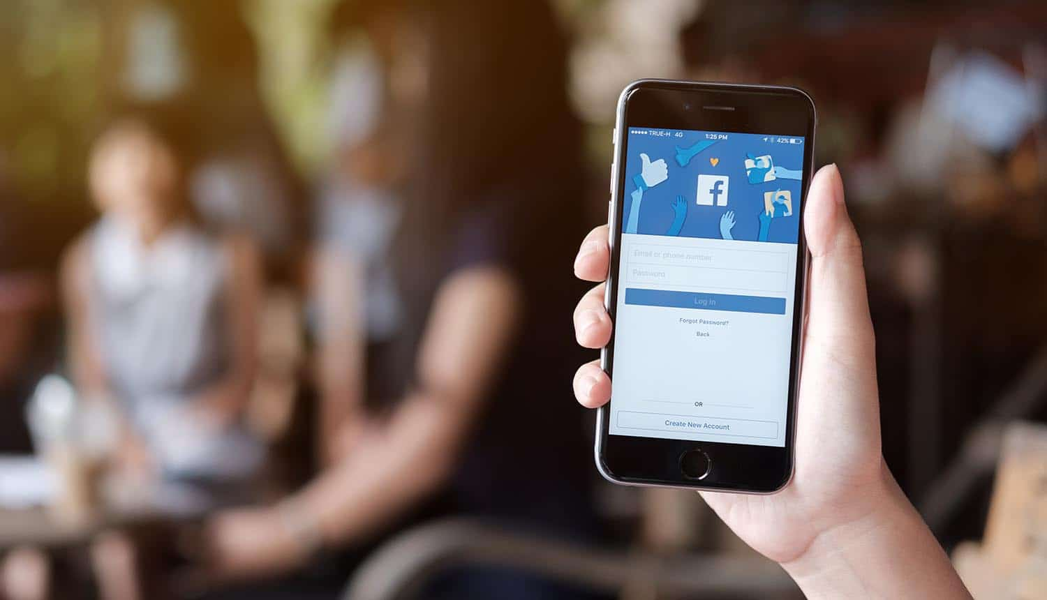 Image of hand holding up mobile phone with the facebook page signifying how your relationship with facebook is complicated