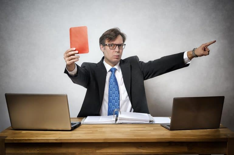 Image of man making judgement and holding up a red card showing the difficulty of regulating privacy as shown by the Facebook Cambridge Analytica case
