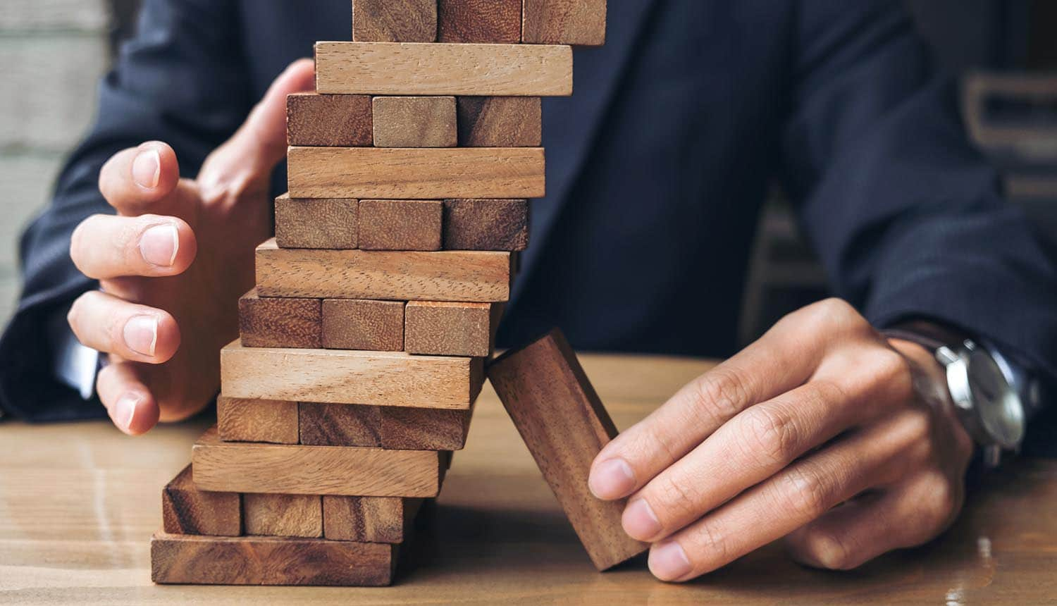Image of man propping up a stack of blocks using a block showing how Big Tech are too big to fail and will require government support