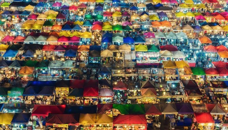 Photo of night market with colorful tents and retail shops