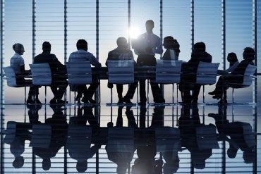 Image of great leadership instead of analyst firms in a boardroom making cyber security decisions