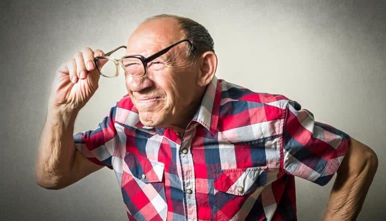 Elderly man peering through glasses