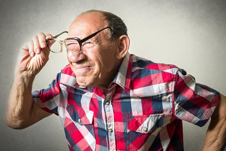 Elderly man peering through glasses