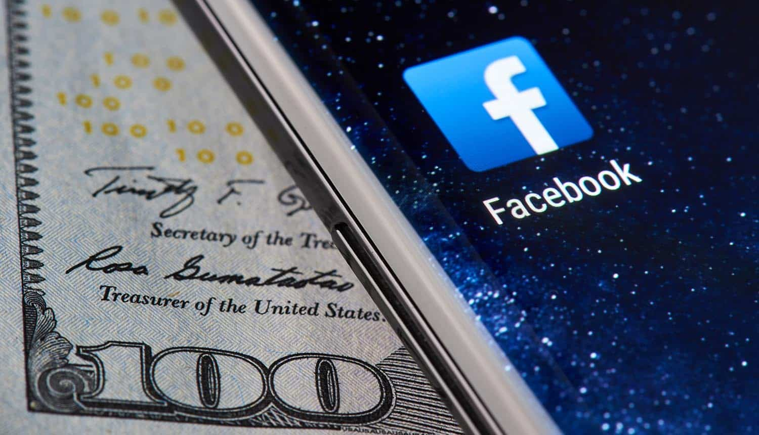 Facebook icon app on smartphone close-up on dollar currency