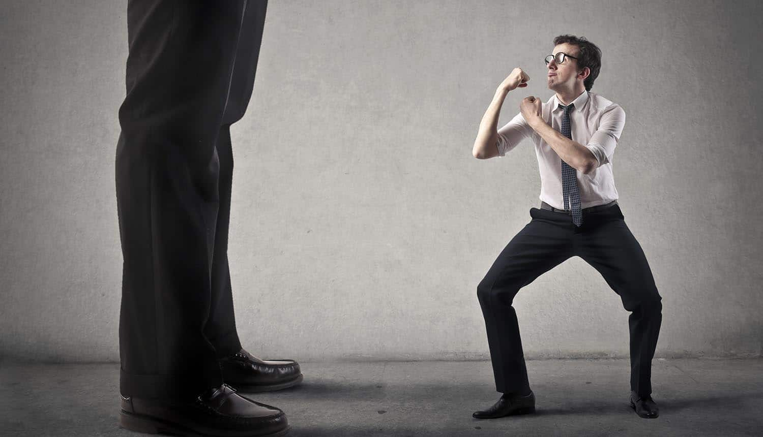 Image of small man fighting corporate giant