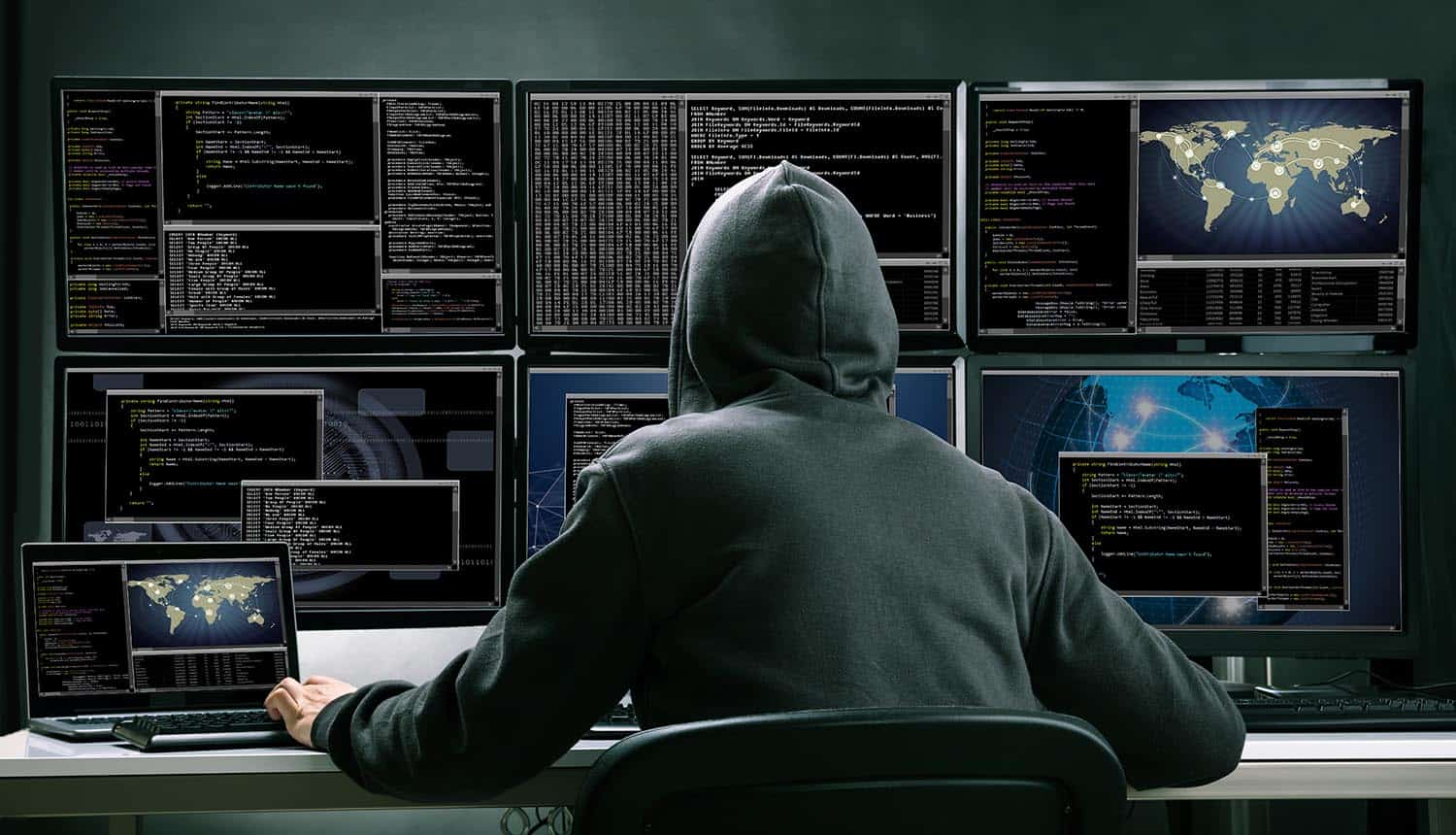 Rear View Of A Hacker Using Multiple Computers