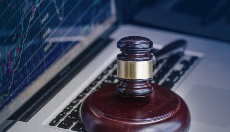 Image of hammer and gavel in front of computer screen as cyber crime legal law concept