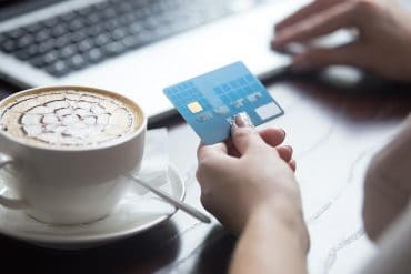 Young beautiful female sitting in modern urban cafe drinking cappuccino and paying with credit card for online shopping on laptop