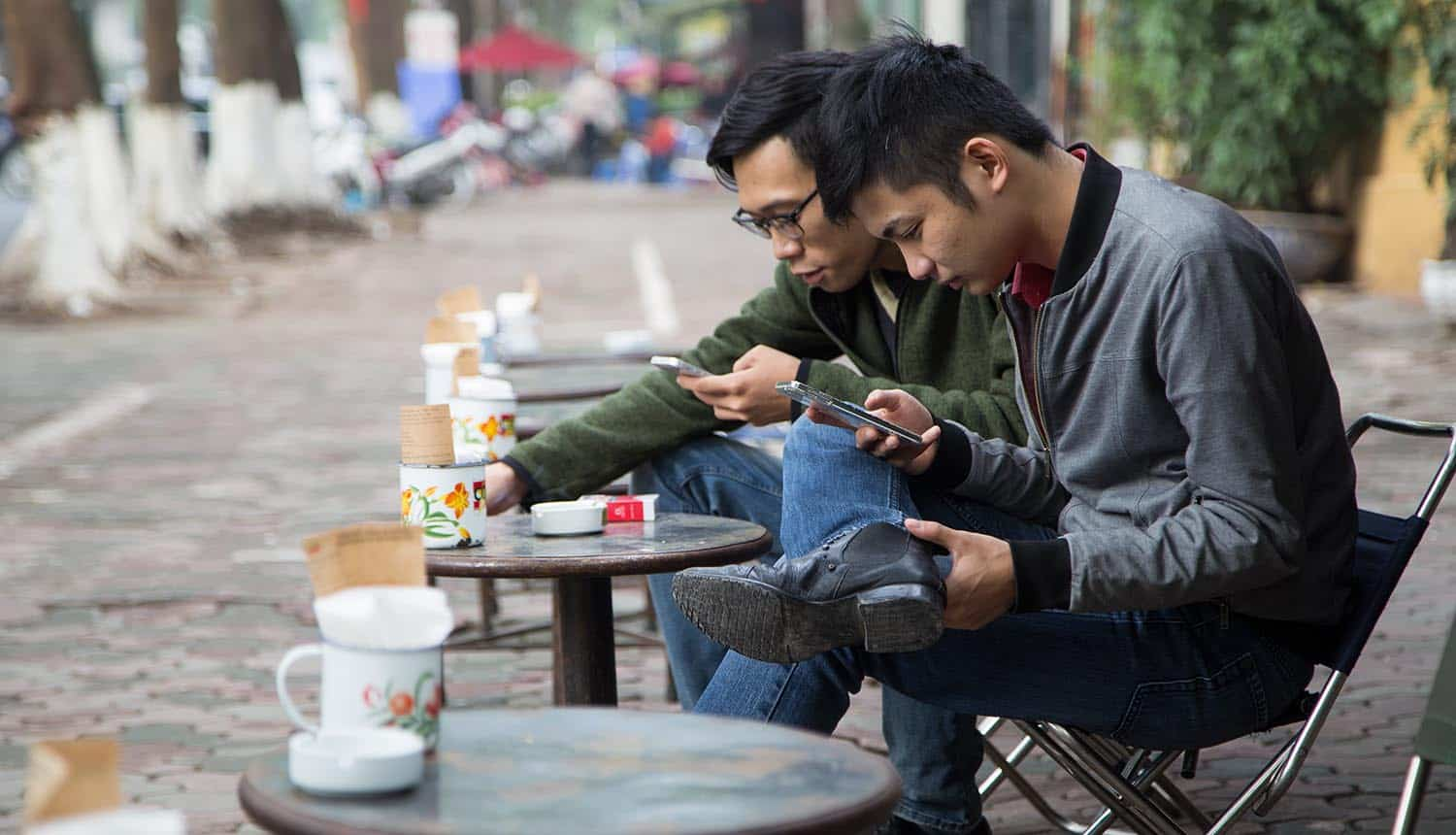 Vietnamese drinking coffee on the sidewalk and using mobile phones