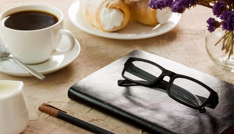 Black leather notepad, black-rimmed spectacles, white coffee cup and rolls with cream for a coffee interview with privacy leaders