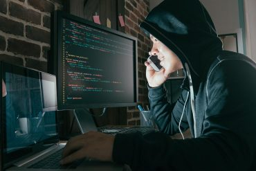 Hacker using mobile smartphone for phishing and ransomware