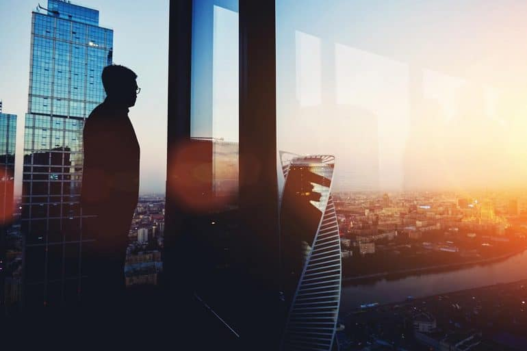 Silhouette of CEO looking out of big office window contemplating