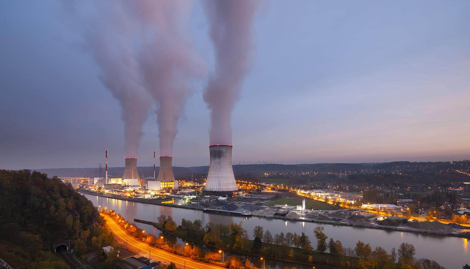 A large nuclear power station on the U.S. power grid by a river at dusk