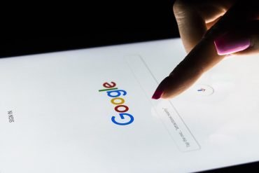 A woman's hand is touching screen on tablet computer for Google search engine.