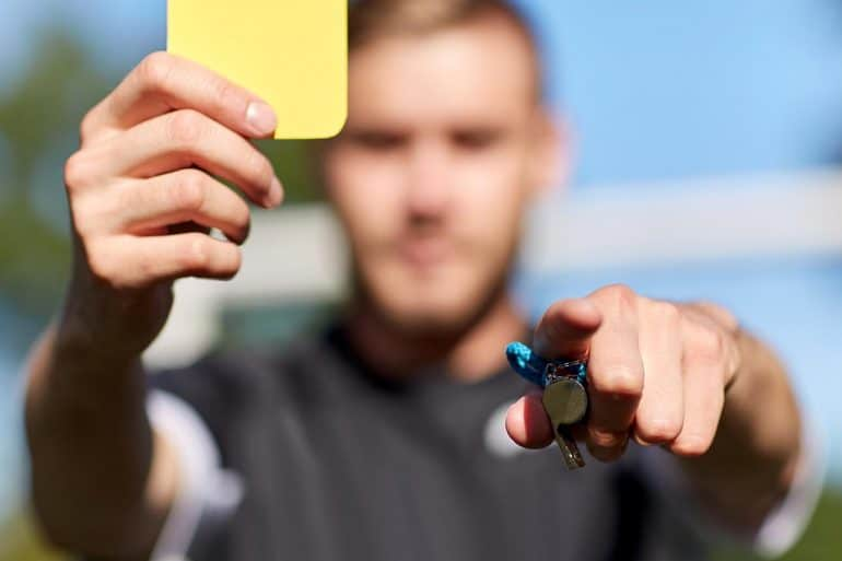 Referee with whistle showing yellow card on football field showing concept of tough regulatory environment for privacy and data security