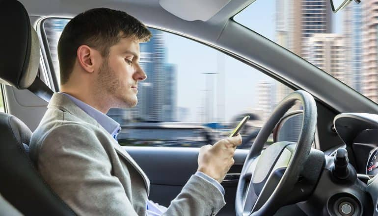 Side View Of A Young Man Sitting Inside Autonomous Vehicle Using Mobile Phone