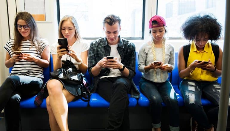 Group of young adult friends using secure messaging app on smartphones in the subway