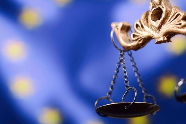 Scales of Justice in front of the European Union flag in the background.