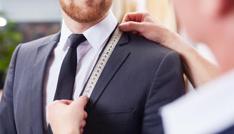 Tailor taking measurements of jacket to fit businessman showing personalization
