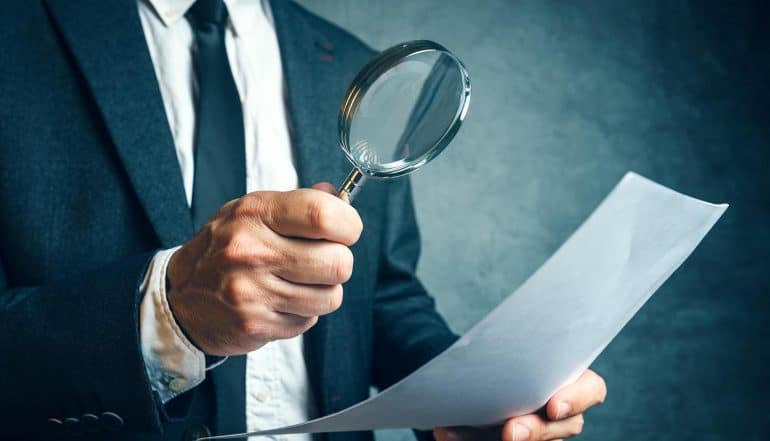 Regulator reviewing EU GDPR compliance documents through magnifying glass