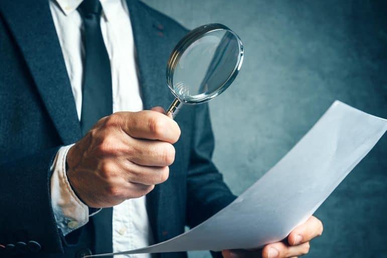 Regulator reviewing EU GDPR compliance documents through magnifying glass