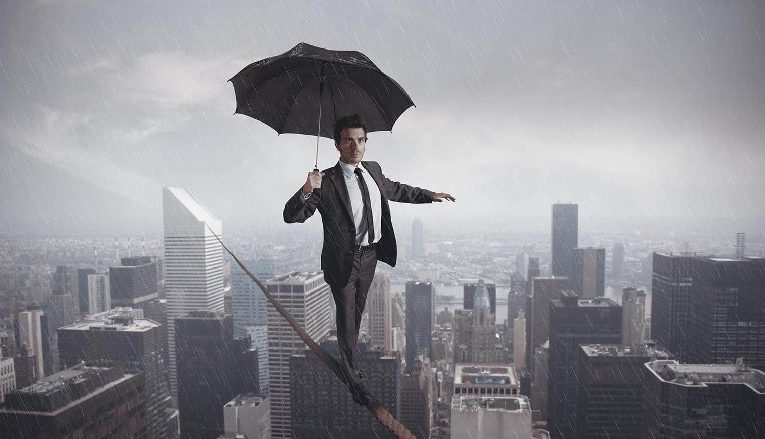Privacy leader balancing on a tight rope carrying umbrella to shield against the rain showing the difficulty of balance and integration