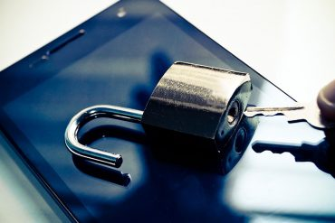 Hand with a key trying to open security lock on a smartphone showing Five Eyes wanting access to data from tech companies