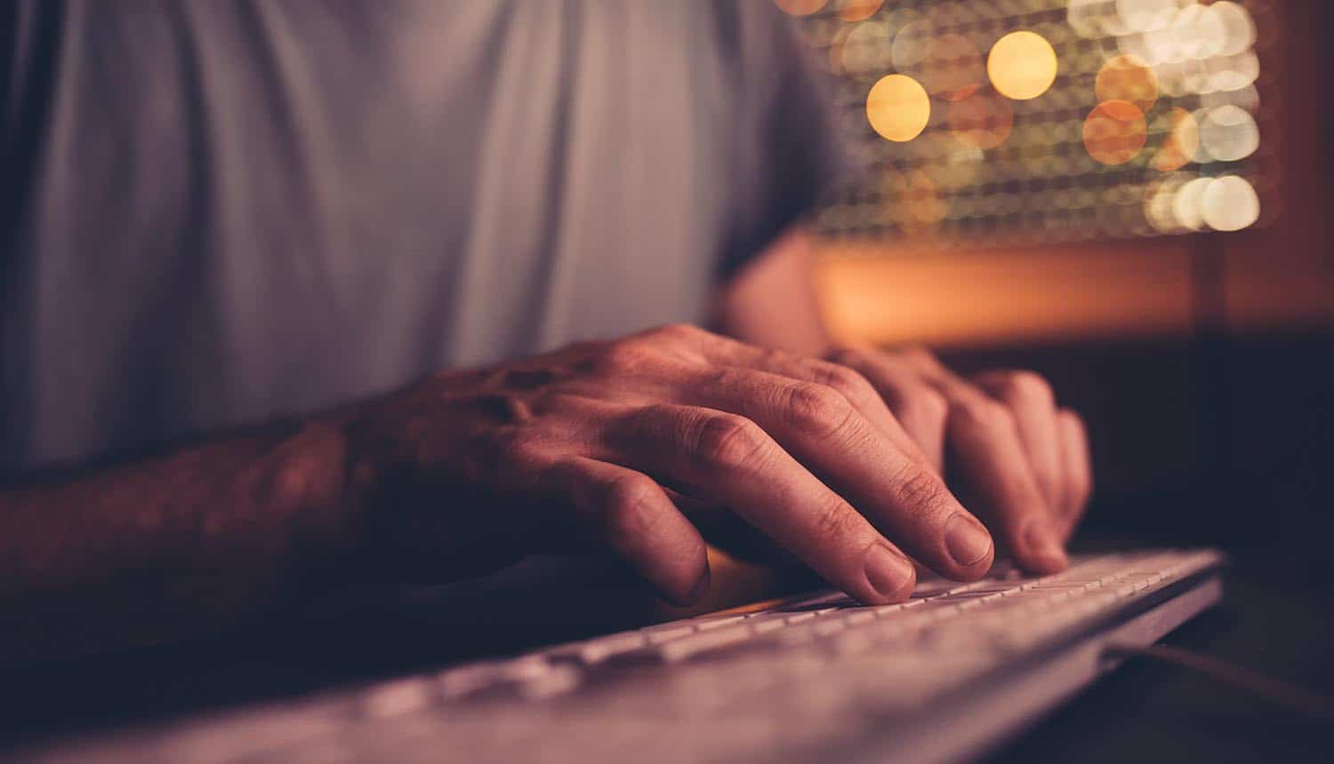 Man typing on keyboard of desktop PC showing the dangers of insider threats