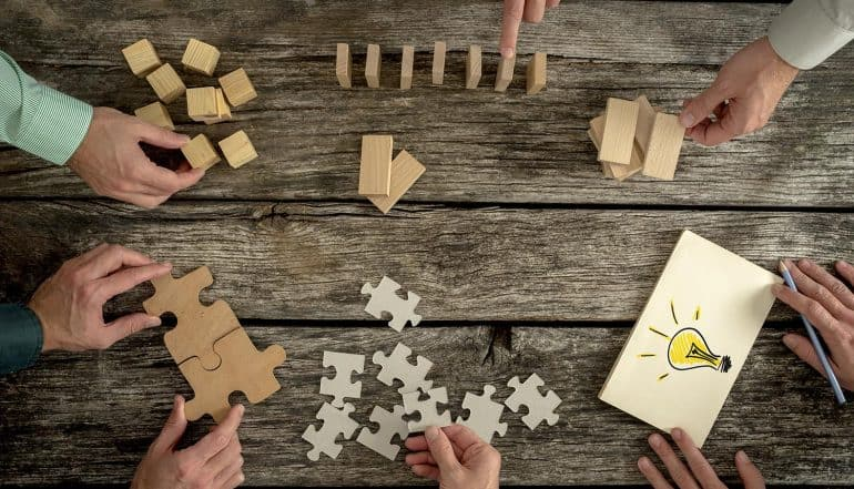 Business executives planning and addressing data privacy and security compliance regulations by holding puzzle pieces creating ideas with light bulb drawn on paper and rearranging wooden blocks