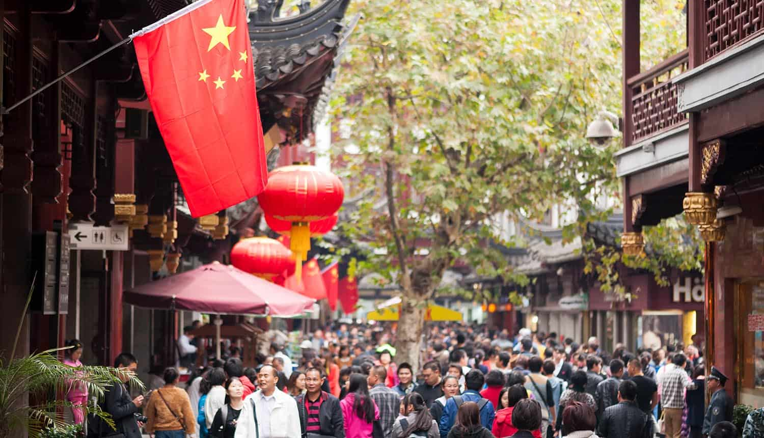 Chinese flag in a crowded old shopping street in China showing the big business of selling customer data