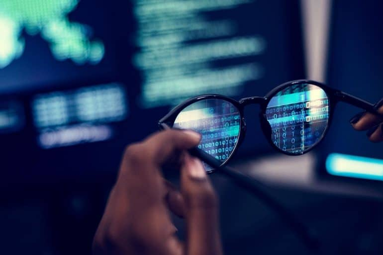 Hands holding glasses in front of computer screen to adopt a hacker's point of view