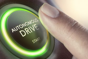 Finger pressing a push button to start an autonomous vehicle and shows the threat of hacking