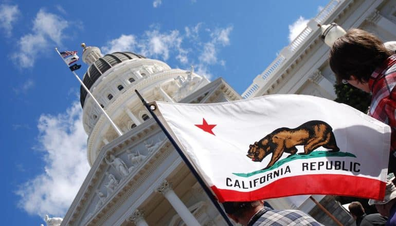 People carrying California state flag at the California State Capitol showing challenges for CCPA compliance