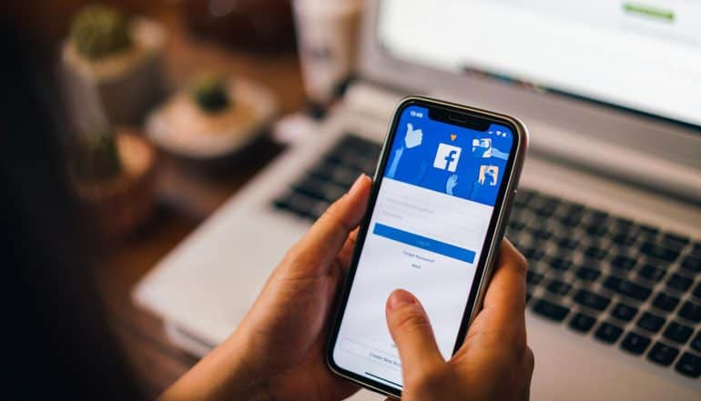 Woman holding a iPhone X and logging into Facebook after Facebook data breach which led to 50 million compromised accounts