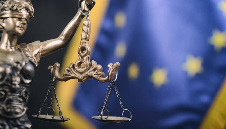Lady Justice in front of the European Union flag in the background showing expectations of EU GDPR fines and sanctions