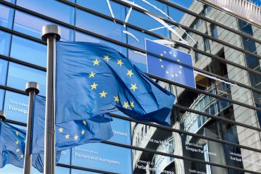 European Union flags in front of the European Parliament in Brussels, Belgium showing uncertainty with GDPR