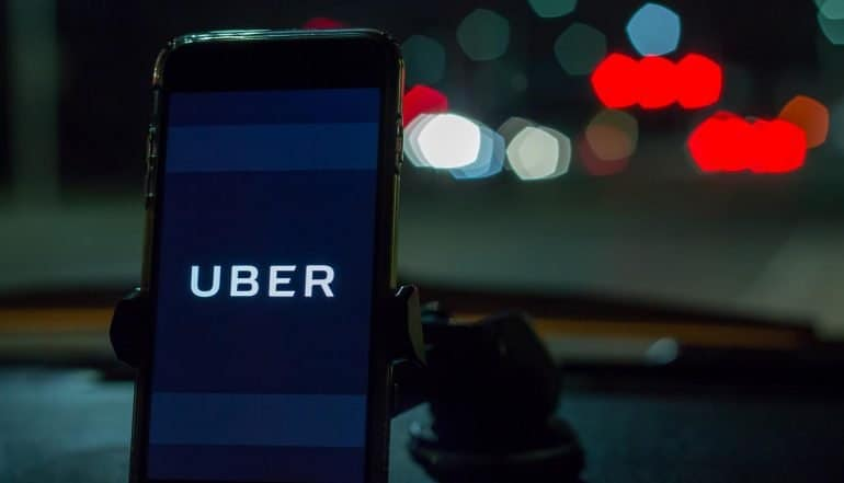 Smartphone attached to a car mount in car with Uber logo at night showing lessons from the Uber breach settlement